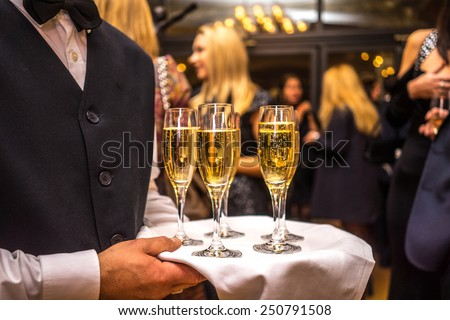 waiter with champagne on a tray - stock photo