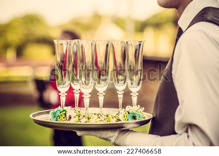 Waiter with glasses on the tray at wedding ceremony, waiting for champagne - stock photo