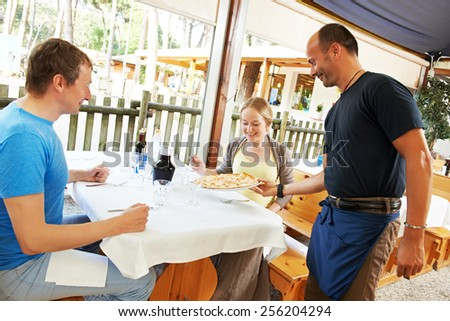 waiter with pizza on plate serving in small italian restaurant - stock photo