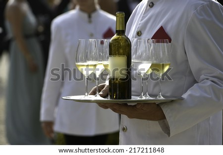 Waiters are serving vine at a wedding outdoor party - stock photo