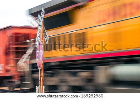 Waiting at a railroad crossing while a fast freight train passes by. - stock photo