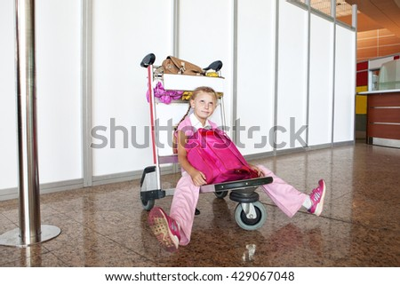 waiting child on the carriage in the airport - stock photo