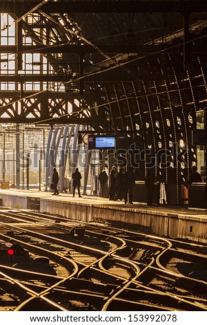 Waiting commuters at a Dutch railway station during sunset - stock photo