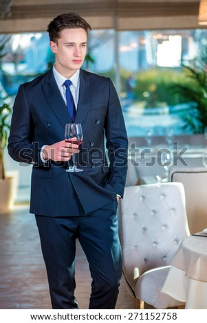 Waiting for a date. Young man businessman in formal wear standing in a restaurant while holding glass of wine and looking forward - stock photo