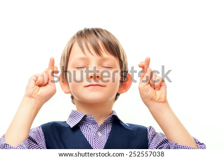 Waiting for a special moment. Closeup of adorable little boy in formalwear keeping his fingers crossed and eyes closed while standing isolated on white background with copy space - stock photo