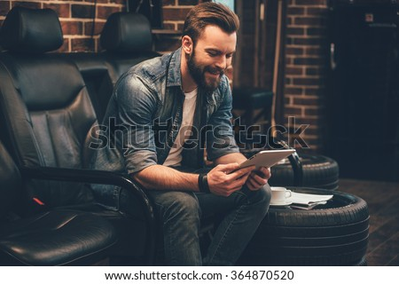Waiting for appointment. Handsome young bearded man working on digital tablet with smile while sitting in comfortable chair at barbershop - stock photo