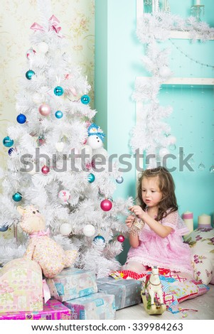 Waiting for Christmas: a beautiful little girl with a winter makeover in a pink dress decorates the new year tree on the background of stylish new year decorations in the style of high key