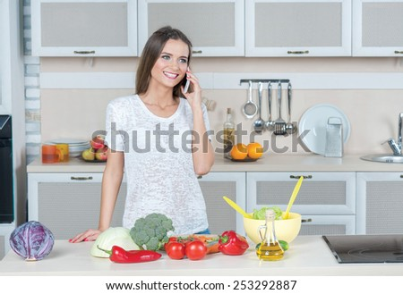 Waiting for dinner on the kitchen. Portrait of young and beautiful girl is preparing salad on the kitchen, while talking with her family on mobile phone
