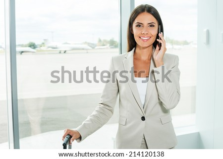 Waiting for flight. Beautiful young businesswoman in formalwear talking on the mobile phone and smiling while standing in airport with airplanes in the background - stock photo