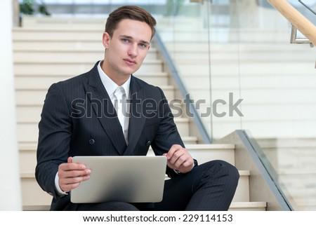 Waiting for good business result. Young and successful businessman is sitting and working with laptop.