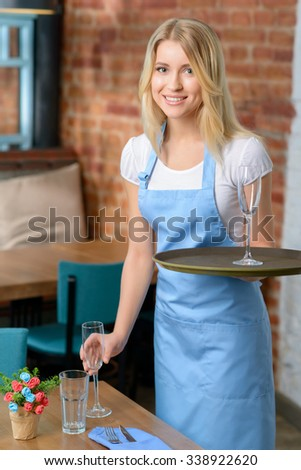 Waiting for guests. Pleasant cheerful delighted waitress holding wineglass and tray while doing her job - stock photo