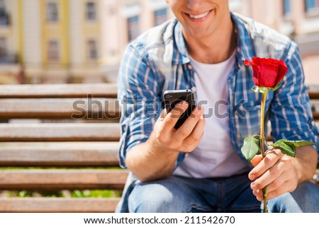 Waiting for her. Close-up of happy young man holding single rose and mobile phone while sitting on the bench - stock photo