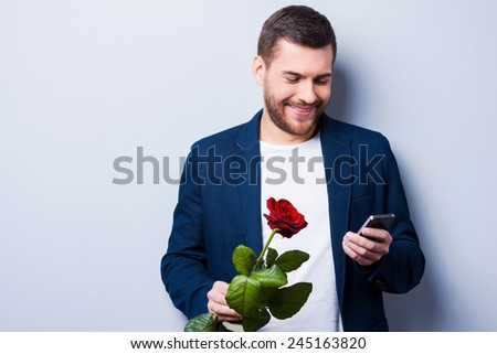 Waiting for her. Handsome young man typing message to his girlfriend while holding a flower and standing against grey background - stock photo