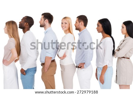 Waiting for her turn. Side view of beautiful young woman looking at camera and smiling while standing in a row with other people and against white background - stock photo