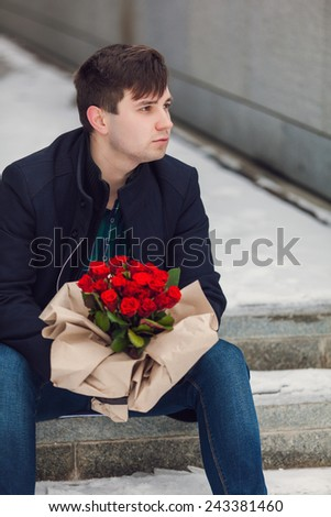 Waiting for his girlfriend. Handsome young man holding bouquet of flowers.
