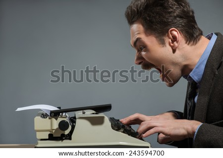 Waiting for idea.  Young nerd author typing something at the typewriter and screaming while sitting at his working place against grey background - stock photo