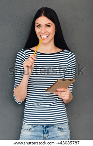 Waiting for inspiration. Attractive young woman holding note pad and carrying pencil in mouth while standing against grey background
