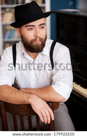 Waiting for inspiration. Portrait of handsome young bearded men sitting in front of his piano - stock photo
