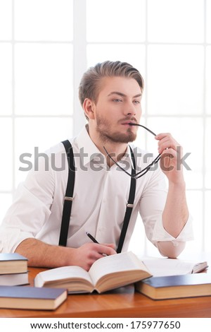 Waiting for inspiration. Thoughtful young man in shirt and suspenders holding glasses and looking away while sitting at his working place - stock photo