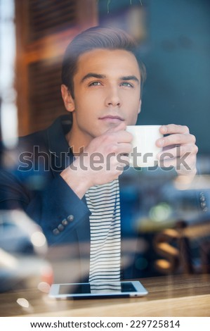 Waiting for inspiration. Through a glass shot of handsome young man writing something in his note pad while enjoying coffee in cafe  - stock photo