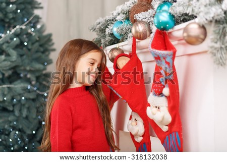 Waiting for present. Pleasant euphoric little girl and holding hand in Christmas stocking while expecting surprise. - stock photo