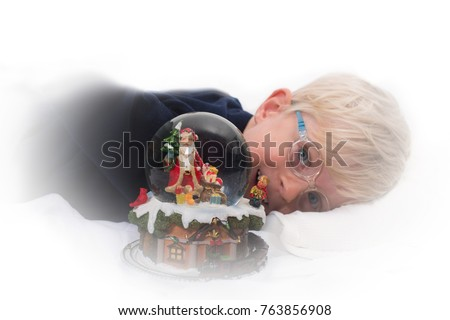 Waiting for Santa Claus: Handsome four year old boy about to sleep next to Christmas music box and snow globe on white background