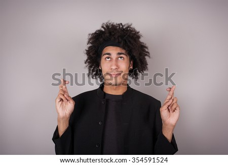 Waiting for special moment. Funny handsome man with his crossed fingers  - stock photo