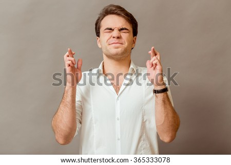 Waiting for special moment. Portrait of young man in a white shirt keeping fingers crossed and eyes closed while standing against a gray background - stock photo