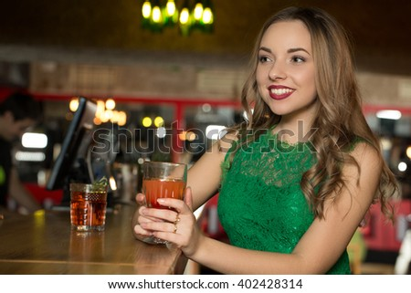 Waiting for you. Beautiful young smiling woman looking happily holding a drink at the bar.