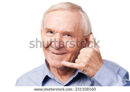 Waiting for your call. Cheerful senior man in shirt gesturing mobile phone near his face and smiling while standing against white background - stock photo