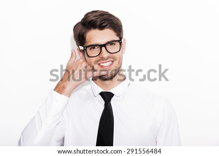 Waiting for your call. Cheerful young man gesturing mobile phone near his face and smiling while standing against white background - stock photo