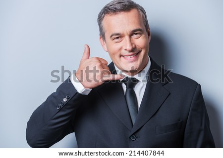 Waiting for your call. Confident mature man in formalwear gesturing mobile phone near his face and smiling while standing against grey background - stock photo