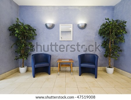 waiting room with blue armchairs and plants - stock photo