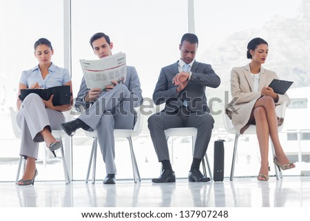 Waiting room with business people sat in line - stock photo