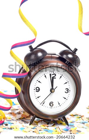 Waiting the New Year with clock, confetti and ribbons. Shallow depth of field