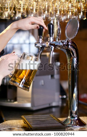 waiting woman pouring beer into the glass - stock photo