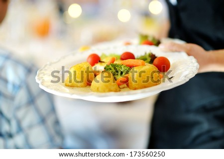 Waitress carrying a plate with vegetable dish - stock photo