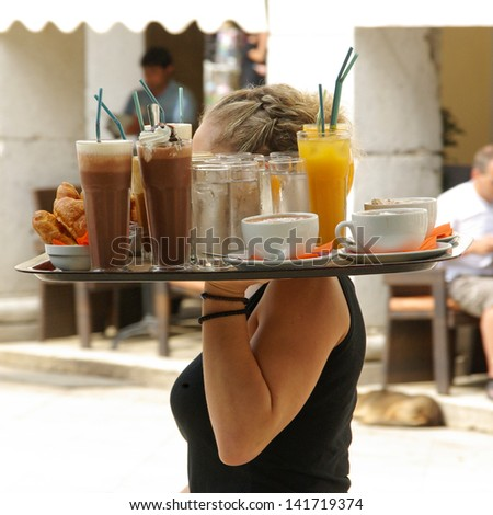 Waitress carrying large tray of drinks in holiday area of Corfu Greece - stock photo