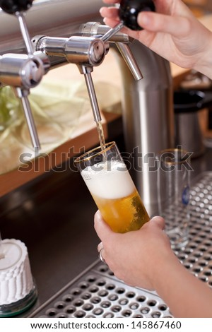 Waitress dispensing draft beer into a pint glass from the metal spigot on a keg in the bar - stock photo