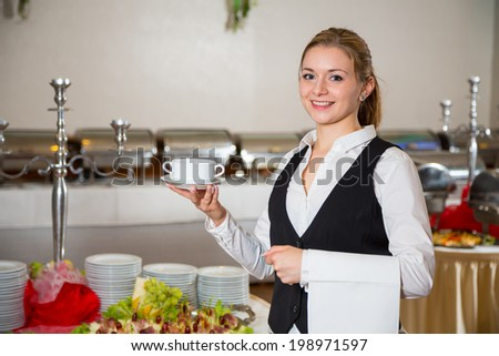 waitress from catering service  in restaurant posing with soup dish