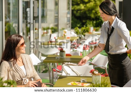 Waitress giving back to woman change money bill restaurant terrace - stock photo