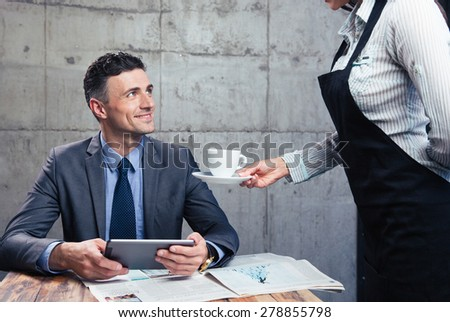 Waitress giving cup with coffee to happy man in suit at restaurant - stock photo