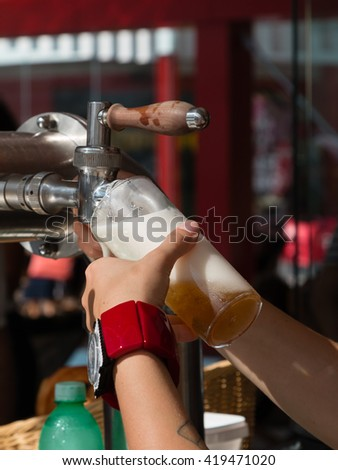 Waitress Hand Pouring a Pint of Beer from the Tap - stock photo