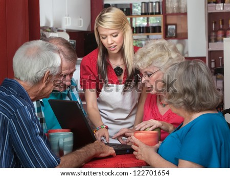 Waitress helping senior citizens with computer in coffeehouse - stock photo