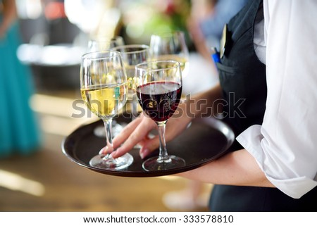 Waitress holding a dish of champagne and wine glasses at some festive event, party or wedding reception - stock photo