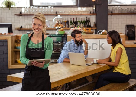 Waitress holding a tablet in the cafe