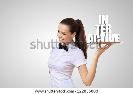 Waitress holding a tray with word interactive on it - stock photo