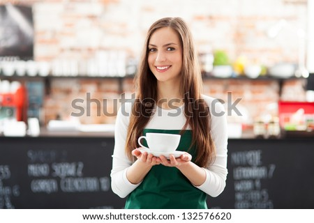 Waitress holding cup of coffee in cafe - stock photo