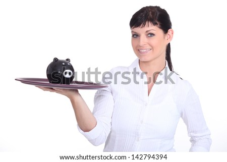 Waitress holding piggy bank - stock photo