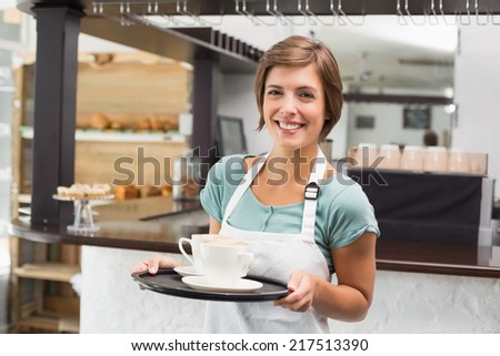 Waitress holding tray with cappuccinos at the coffee shop - stock photo